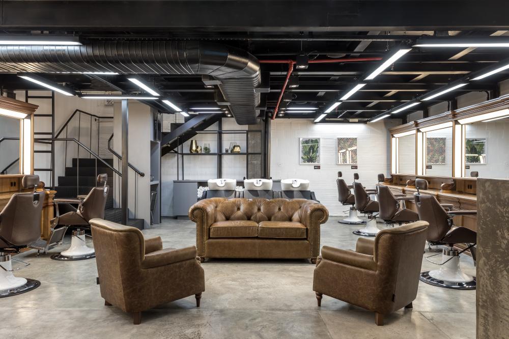 Elementos inspirados em clubes londrinos na arquitetura do maior espaço de beleza masculino de Curitiba.